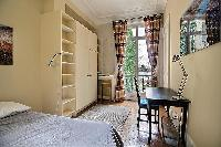 second bedroom with a queen-size bed, built-in shelves and cabinets, and a study desk with a lamp an