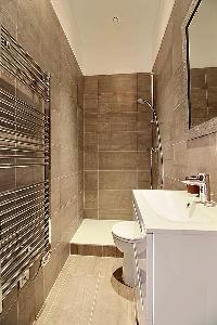 sleek bathroom with sink, bathroom cabinet, mirror, toilet, and shower area in a 3-bedroom Paris lux