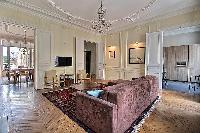 elegant living area and dining room with a six-seater dining set in a 3-bedroom Paris luxury apartme