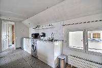 space-efficient kitchen and a washing machine in a 2-bedroom Paris luxury apartment