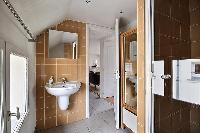 bathroom fully-equipped with a toilet, a sink, a mirror, and a shower area in a 2-bedroom Paris luxu