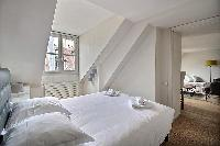 first bedroom with a queen-size bed, and a bedside table with a lamp in a 2-bedroom Paris luxury apa