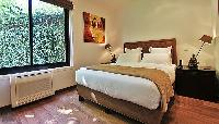 first bedroom furnished with a queen-size bed, and two bedside tables with lamps in a 2-bedroom pari