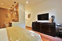 first bedroom furnished with a queen-size bed, mounted flat screen  TV, and an en suite bathroom in