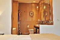 first bedroom with an en-suite open-plan bathroom with a toilet, double sinks, bathroom shelves, a m