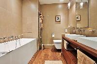 an en-suite open-plan bathroom with a toilet, double sinks, bathroom shelves, a mirror, and a bathtu