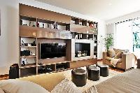 living area furnished with an L-shaped couch, a chair, a center table, modern centerpieces, and a me
