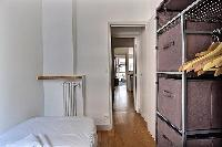 third bedroom with a single bed, a bedside table, and shelves with pull out baskets in Paris luxury