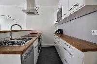 small yet fully-equipped kitchen in a 3-bedroom Paris luxury apartment