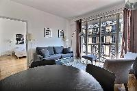 living area with a sofa with access to the bedroom in a 3-bedroom Paris luxury apartment