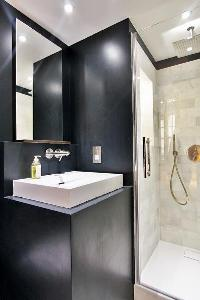 an en-suite bathroom with a toilet, a sink, a mirror, and a shower area in a 2-bedroom Paris luxury
