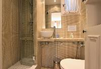 an en-suite bathroom with a toilet, a sink, a mirror, bathroom shelves, and a shower area with a det