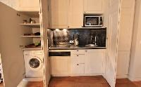 space-efficient fully-equipped cupboard kitchen in a 2-bedroom Paris luxury apartment