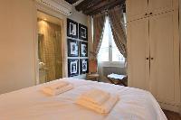 second bedroom with queen-size bed, desk, chair, cabinet, and en-suite bathroom in a 2-bedroom Paris