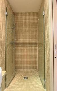 an en-suite bathroom with toilet, sink, mirror, cabinet, and a shower area in a 2-bedroom Paris luxu