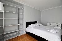 second bedroom with shelves and a Double bed in a 3-bedroom Paris luxury apartment