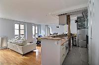 a large and open kitchen, living and dining area in a 3-bedroom Paris luxury apartment