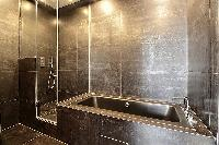 a full bathroom with an open shower, bathtub, double sink and a toilet in a 2-bedroom Paris luxury a