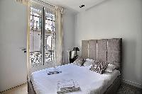 bedroom with a queen size bed in a 2-bedroom Paris luxury apartment