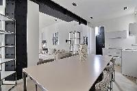 a dining table seats up to six guests in a 2-bedroom Paris luxury apartment