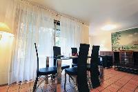 modern dining area for 6 with glass dining table and tall French windows in a 3-bedroom Paris luxury