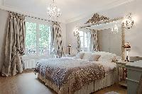elegant bedroom with queen size bed, bedside tables, lamps, wide mirror, bright French windows and d