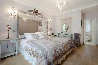 elegant bedroom with queen size bed, bedside tables, lamps, wide mirror, and en suite bathroom in a