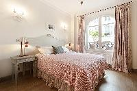 second bedroom with queen size bed, bedside tables, lamps, bright French windows and drape curtains