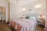 second bedroom with queen size bed, bedside tables, lamps, and closets in a 3-bedroom Paris luxury a