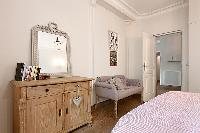 elegant bedroom with queen size bed, armchair, mirror, and cabinet in a 3-bedroom Paris luxury apart