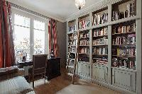 study room with a sofa bed and bookshelves in a 3-bedroom Paris luxury apartment