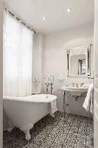 elegant bathrooms with sinks, shower, bathtub and toilet in a 3-bedroom Paris luxury apartment