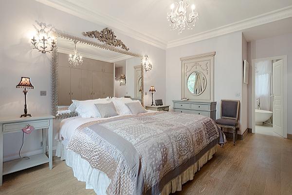 elegant bedroom with queen size bed, bedside tables, lamps, wide mirror, and en suite bathroom in a