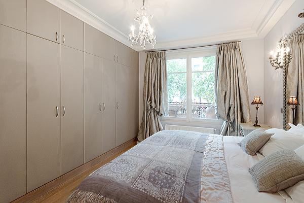 elegant bedroom with queen size bed, bedside tables, lamps, and closets in a 3-bedroom Paris luxury