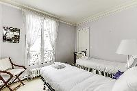 Second Bedroom with two single beds and more closet space in a 2-bedroom Paris luxury apartment