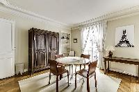 Dining Room with a glass round table and 4 seats in a 2-bedroom Paris luxury apartment