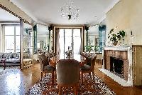 classy dining room for eight with a long table, chandelier, and decorative fireplace with access to
