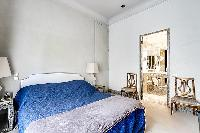 chic bedroom with television and bright windows with drape curtain in paris luxury apartment