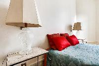 a styish lamp beside the bed in a 3-bedroom paris luxury apartment