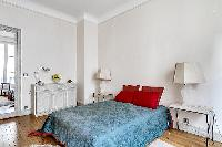 chic bedroom with lamp, bright windows, and drape curtain in a 3-bedroom paris luxury apartment