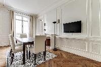 elegant Dining Room with a TV and decorative fireplace in a 2-bedroom Paris luxury apartment