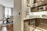 modern Kitchen with a little window to look into the dining room in a 2-bedroom Paris luxury apartme
