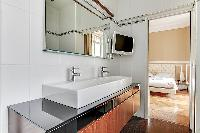 elegant en suite bathroom with sink and mirror in a 2-bedroom Paris luxury apartment