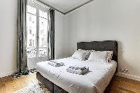 Bedroom with a queen size bed and plenty of closet space in a 1-bedroom Paris flat