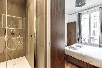 Bedroom with a queen size bed and an en-suite bathroom with a standing shower, toilet and sink in a