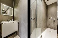 an en-suite bathroom with a standing shower, toilet and sink in a 1-bedroom Paris flat