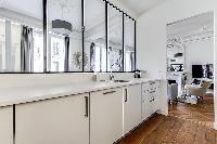 semi-open kitchen view-able by windows  in a 2-bedroom Paris luxury apartment