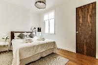 Bedroom with Queen size bed, bedside tables, and lamps in a 2-bedroom Paris luxury apartment