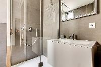bathroom with standing shower and toilet  in a 2-bedroom Paris luxury apartment
