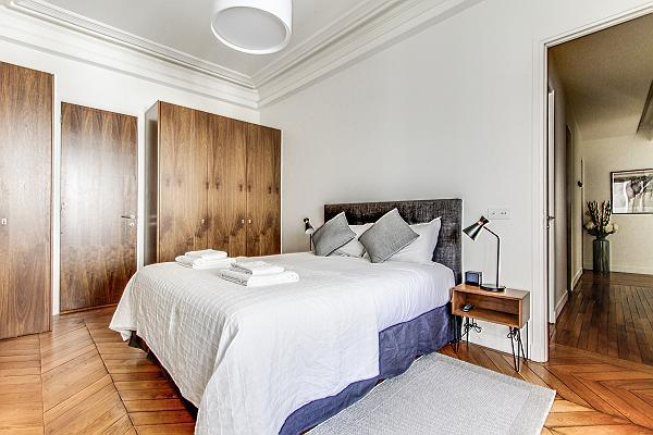 Bedroom with Queen size bed, bedside tables, lamps, and plenty of closets in a 2-bedroom Paris luxur